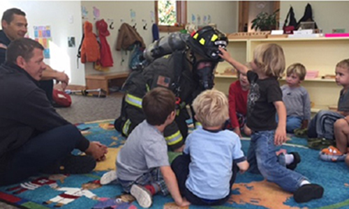 big sky firefighter with a group of children at a school